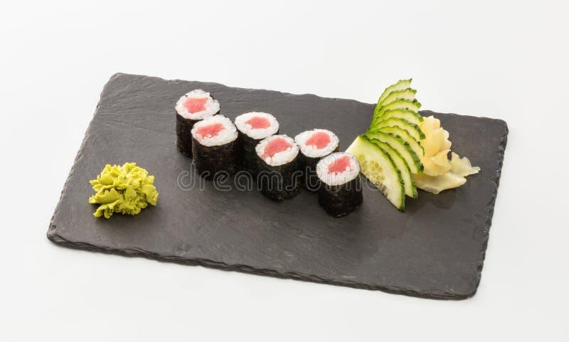Rolos de sushi com salmões em uma placa preta isolada em um CCB branco foto de stock