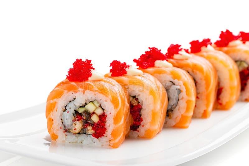Rolos de sushi com salmões, enguia, pepino e tobiko na placa branca fotos de stock royalty free