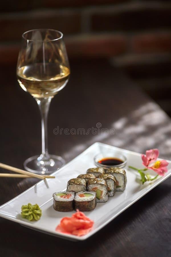 Rolos de sushi na placa branca e no vidro do vinho, verticais imagens de stock