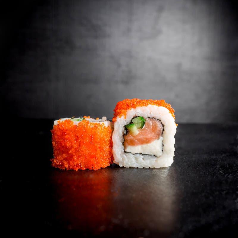 Rolos de sushi no fundo preto Alimento japonês imagens de stock