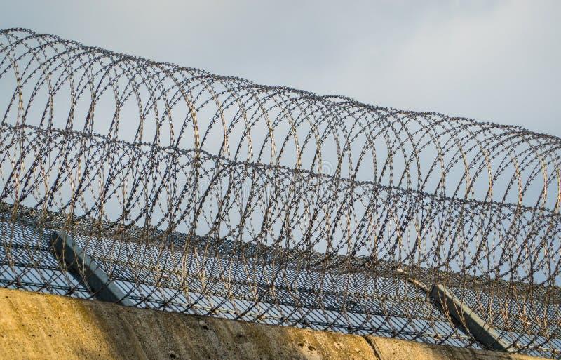 Rolos do arame farpado na borda da parede de uma prisão em Alemanha fotografia de stock