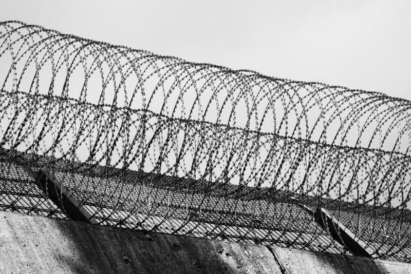 Rolos do arame farpado na borda da parede de uma prisão em Alemanha, preto e branco foto de stock