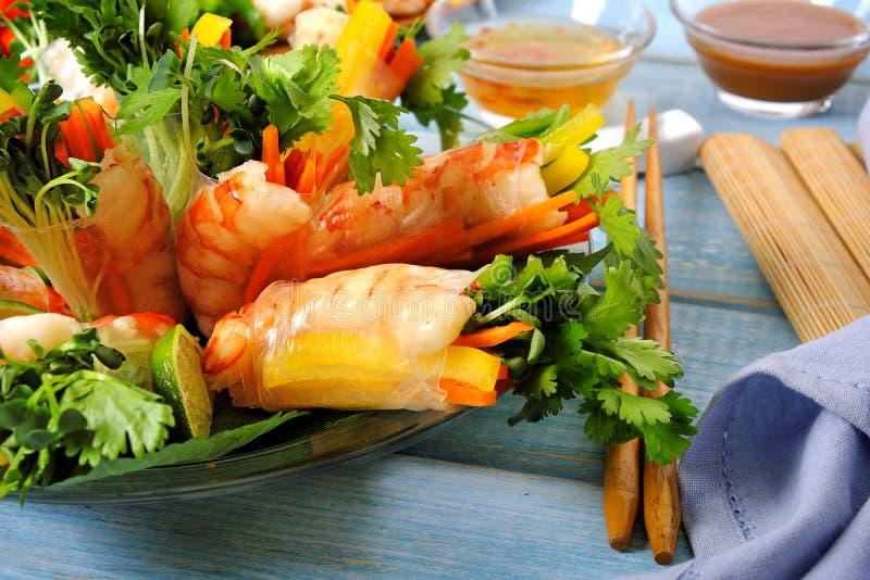 Rolos do vietnamita com o camarão e os vegetais envolvidos no papel de arroz com hashis foto de stock
