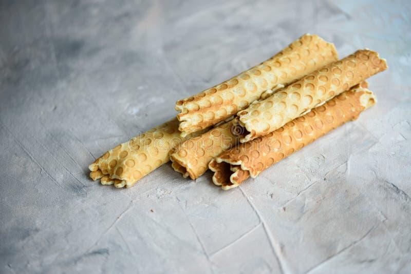 Rolos do waffle, saboroso e perfumado, com leite condensado fervido em um fundo concreto imagens de stock