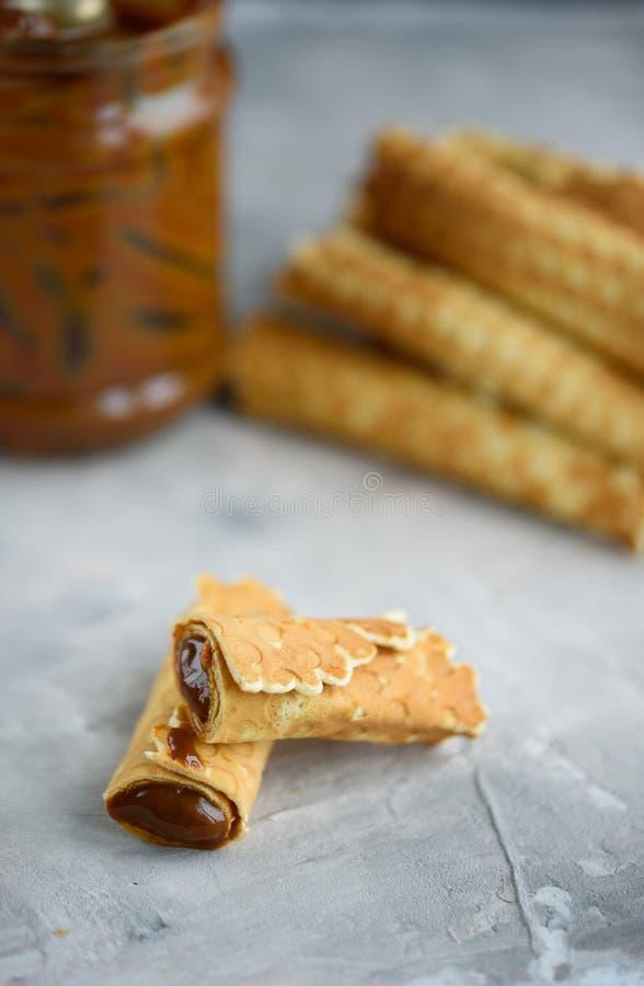 Rolos do waffle, saboroso e perfumado, com leite condensado fervido em um fundo concreto foto de stock