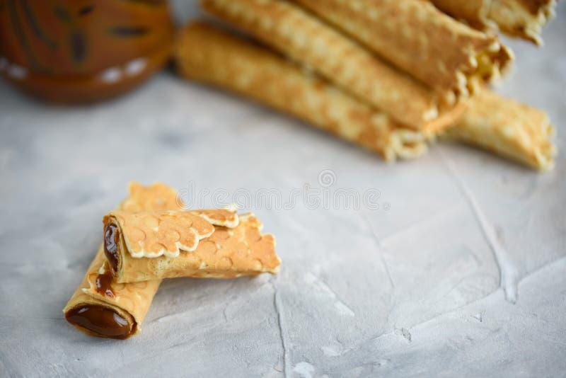 Rolos do waffle, saboroso e perfumado, com leite condensado fervido em um fundo concreto fotografia de stock