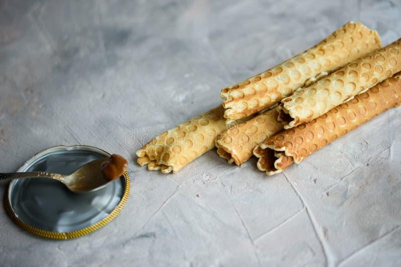 Rolos do waffle, saboroso e perfumado, com leite condensado fervido em um fundo concreto imagem de stock royalty free