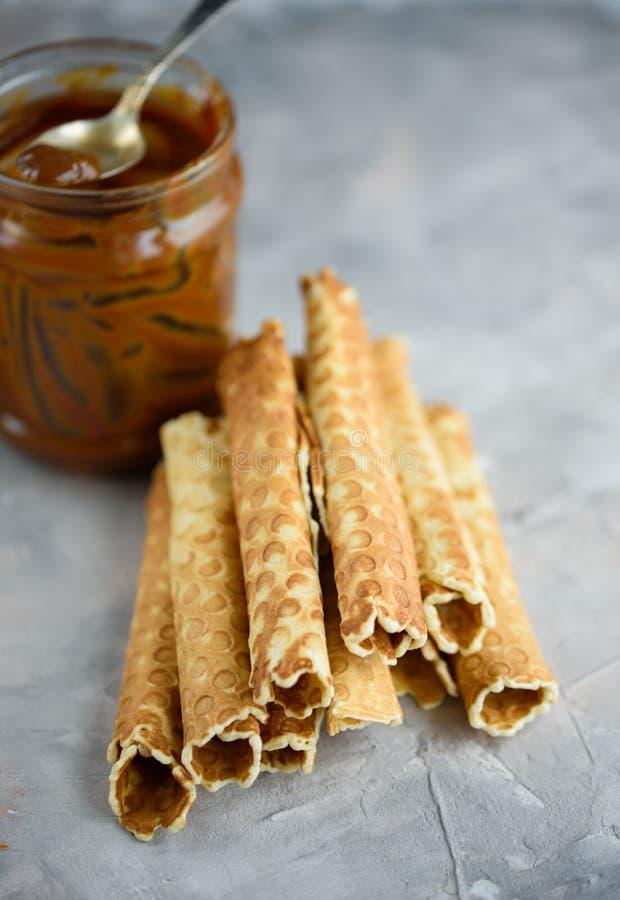 Rolos do waffle, saboroso e perfumado, com leite condensado fervido em um fundo concreto imagem de stock