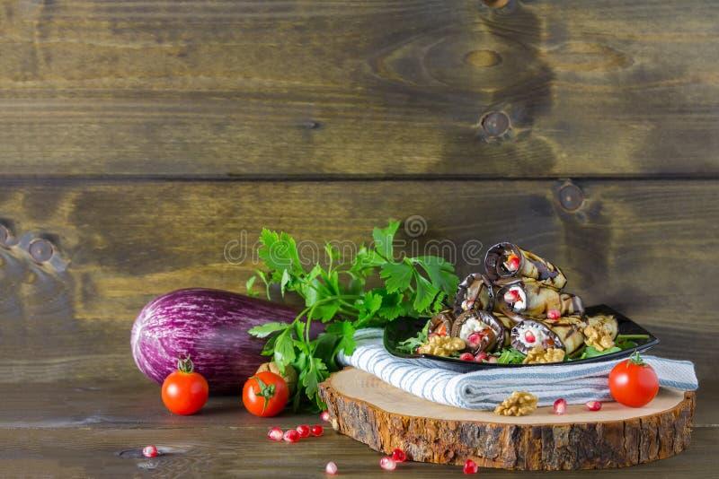 Rolos grelhados das beringelas com porcas, queijo, alho e ervas e sementes da romã, culinária georgian no fundo de madeira fotografia de stock