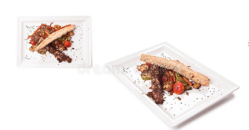 Rolos Roasted do peito de frango envolvidos em fatias do bacon, servido com batatas fritadas e os vegetais cozinhados isolados no imagens de stock royalty free