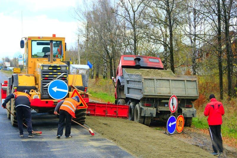 Rolownik i naprawy drużyna robimy naprawie asfaltująca droga obraz stock