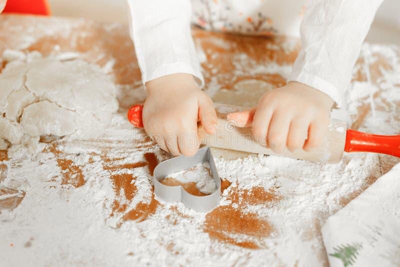 Rolt het Unrecongnizable die kleine kind gebakje met deegrol op, met koekjessnijder wordt omringd in vorm van hart, die gaan aan royalty-vrije stock afbeelding