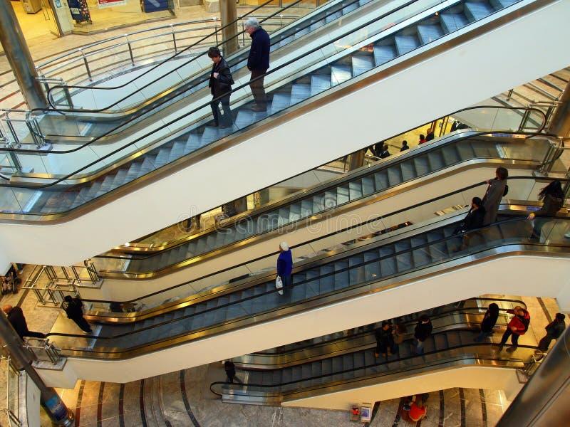 Roltrappen op verscheidene niveaus van winkelcentrum stock afbeelding
