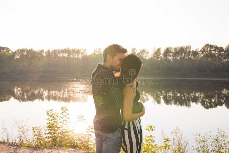 Romántico, amor, concepto de la gente - par joven que abraza cerca del lago en la puesta del sol fotos de archivo libres de regalías
