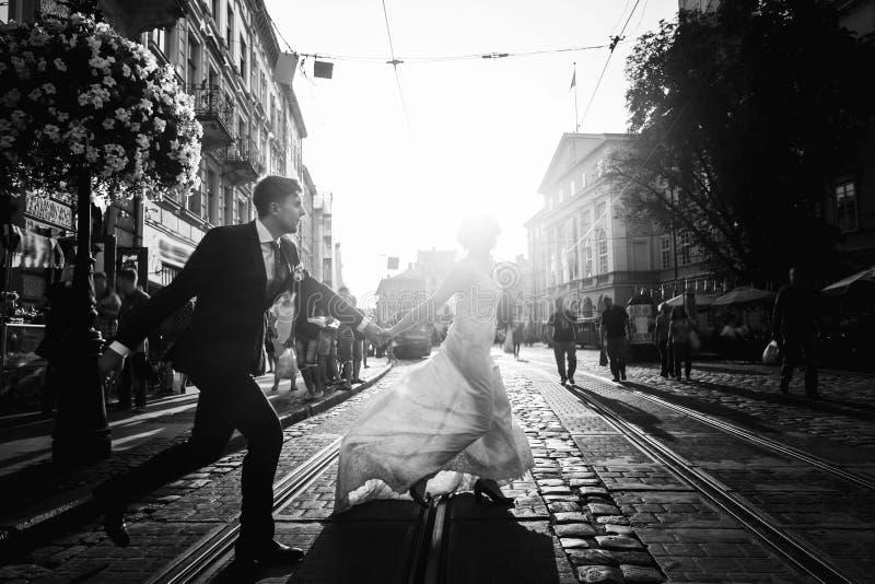 Romântico, pares do recém-casado do divertimento que correm através de pavimentar a estrada na cidade fotografia de stock royalty free