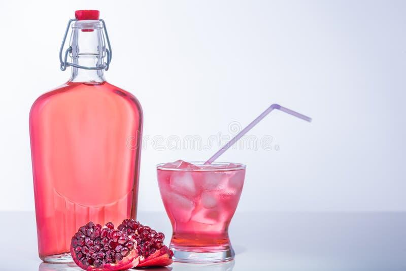 Romã com Juice Bottle e vidro completo com gelo e palha fotos de stock royalty free