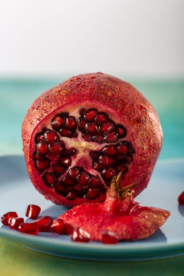 Romã e sementes vermelhas do fruto em uma placa azul Fruto tropical brilhante bonito imagens de stock royalty free