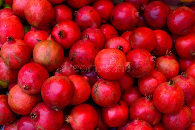 Romã maduras vermelhas como o fundo Uma pilha das romã em um contador, fim acima fotos de stock