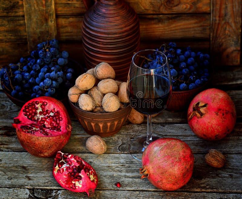 Romã, nozes e vidro do vinho imagem de stock royalty free