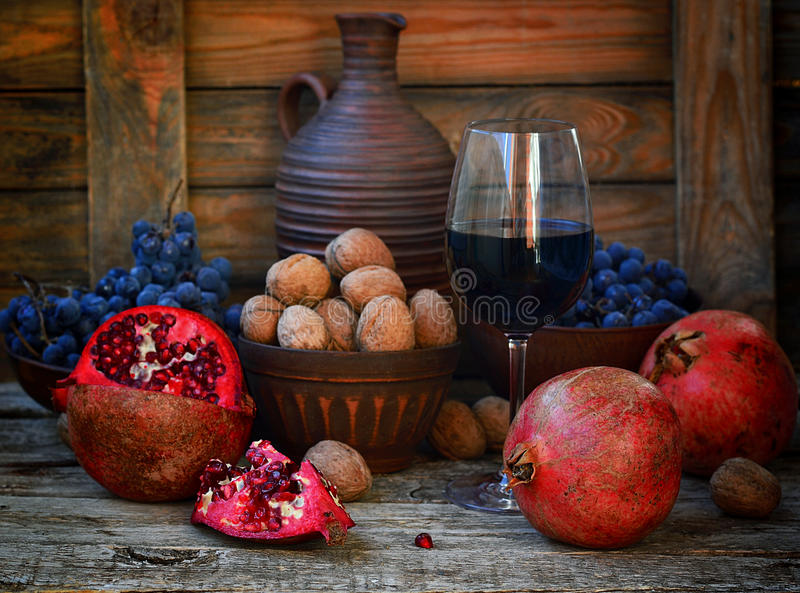 Romã, nozes e vidro do vinho imagem de stock
