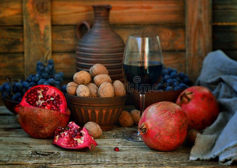 Romã, nozes e vidro do vinho fotos de stock