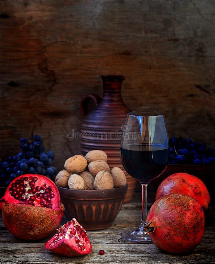 Romã, nozes, uvas e vinho imagens de stock