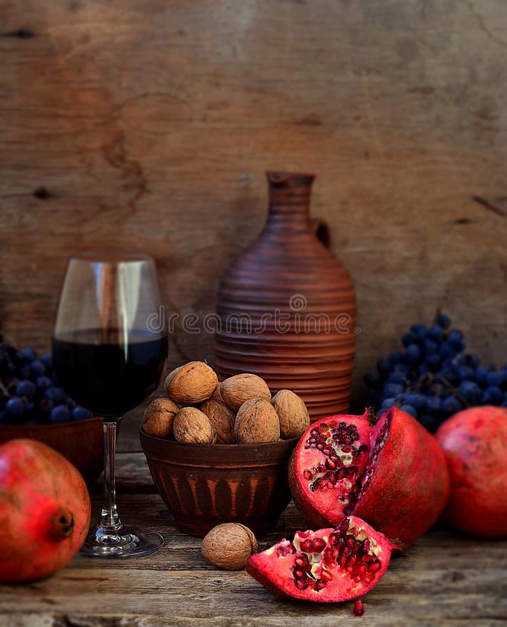 Romã, nozes, uvas e vinho imagem de stock