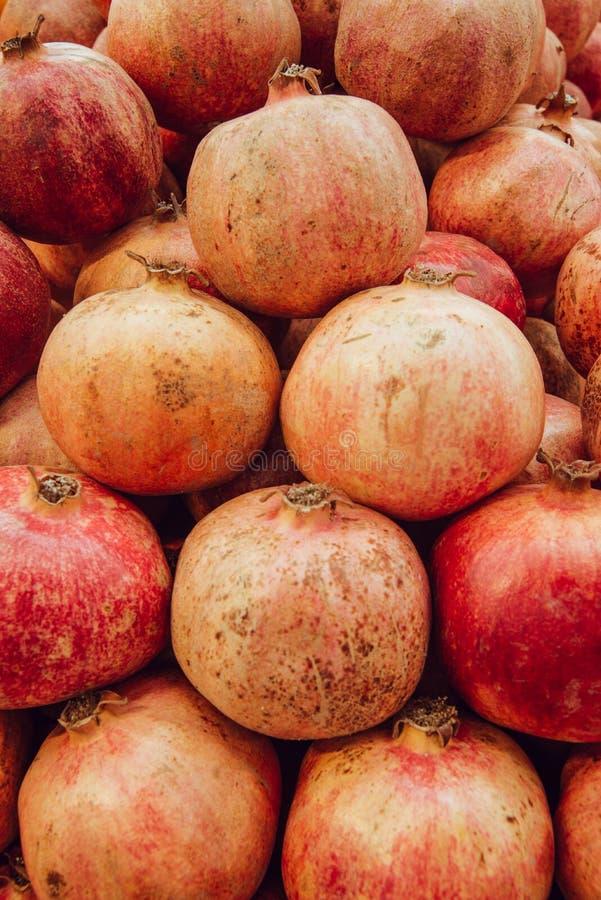 A romã vermelha do suco no fundo escuro o fruto aberto de uma romã encontra-se em um monte das romã imagem de stock