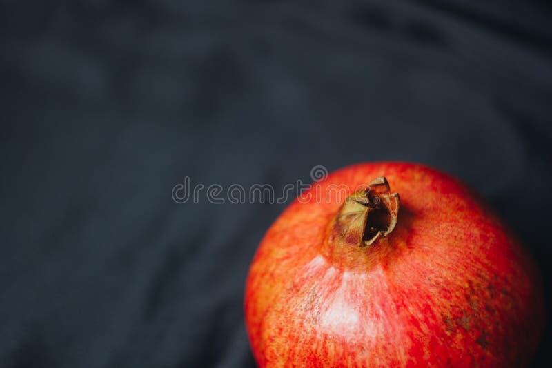 Romã vermelha inteira madura em um fundo preto da tela, sementes da romã, fim acima, vida imóvel isolada, fruto oriental imagens de stock
