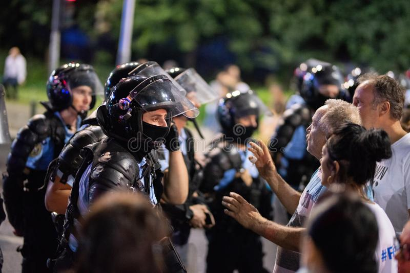 Romênia, Bucareste - 10 de agosto de 2018: Agentes da polícia que discutem com os protestadores calmos antes de um episódio mais  imagem de stock royalty free