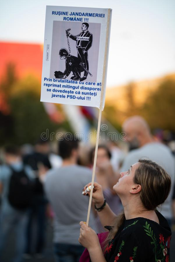 Romênia, Bucareste - 12 de agosto de 2018: O protestador que guardam o sinal e as lágrimas após os cidadãos gased fotografia de stock royalty free