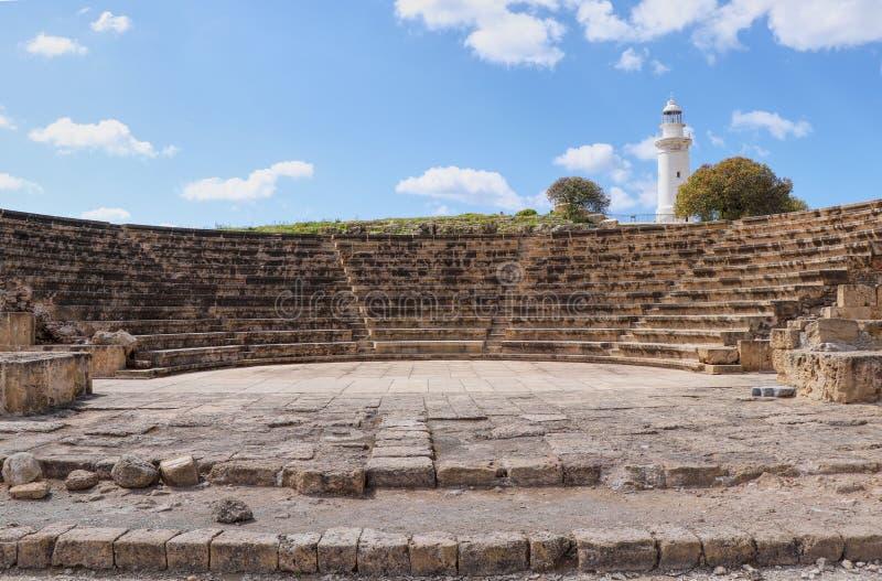 Rom-ampitheatre für irgendeine Gelegenheit in Paphos Altes Theater mit weißem Leuchtturm im Hintergrund, in Pafos, Zypern lizenzfreies stockfoto