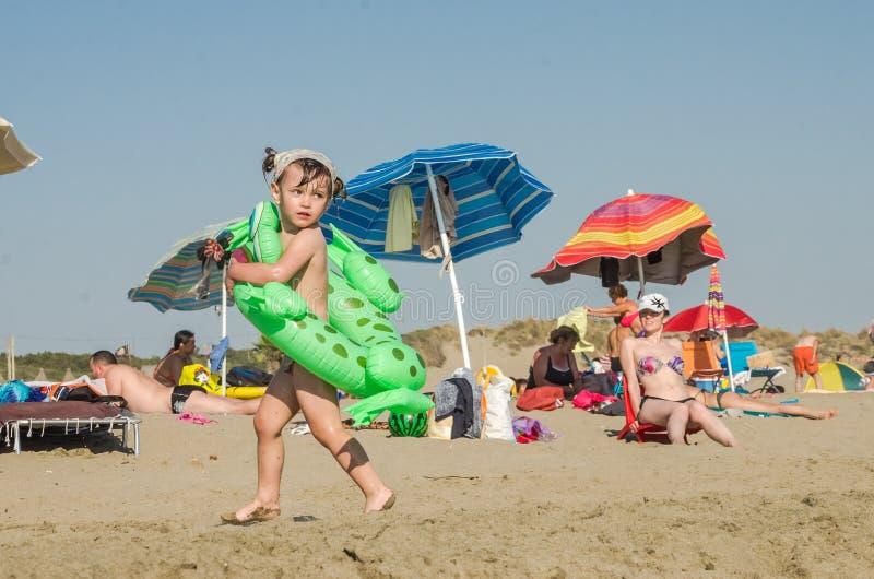 ROM, ITALIEN - JULI 2017: Kleines reizend Mädchen, das auf einem sandigen Strand mit einem aufblasbaren Kreis mit einer Freundin  lizenzfreies stockfoto