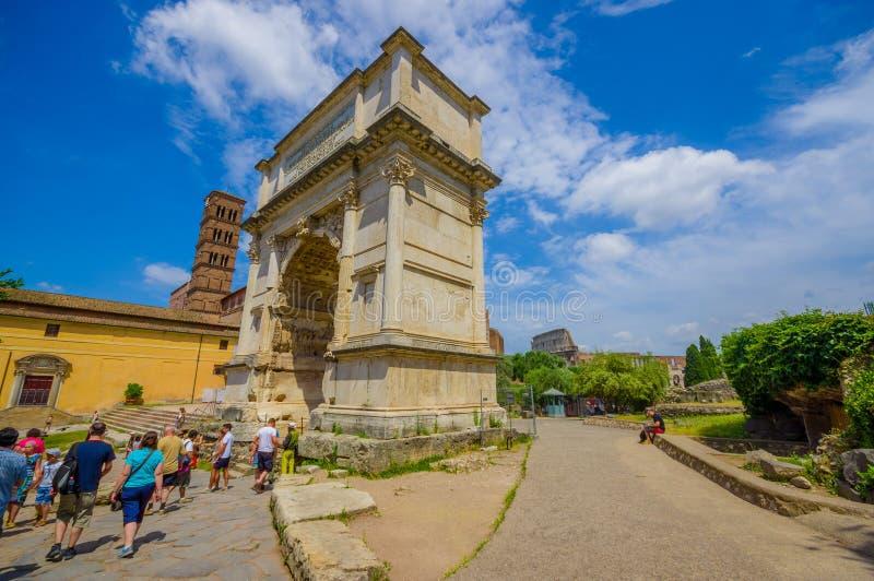 ROM, ITALIEN - 13. JUNI 2015: Leute kommen zu Roman Forum, großer Steinbogen mit römischen Buchstaben herein Bäume ganz um den Pl stockfotografie