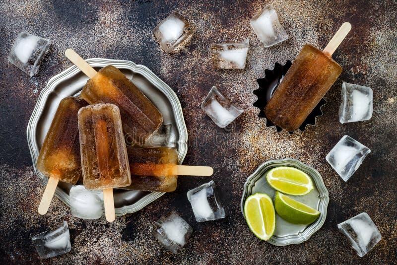 Rom- och colacoctailisglassar med limefruktfruktsaft Hemlagade fryste alkoholiserade paletas för Kubalibre - is poppar Över huvud arkivbilder