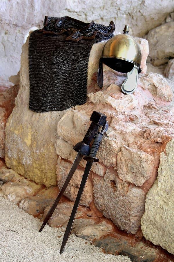 Romański mosiężny hełm, opancerzona tunika i dwa krótkiego kordzika opiera, fotografia royalty free