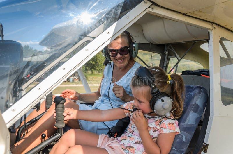 ROMA, ИТАЛИЯ - АВГУСТ 2018: Женский ребенок инструктора и маленькой девочки у руля легкого воздушного судна стоковые изображения