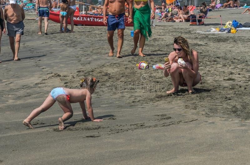 ROMA, ИТАЛИЯ - АВГУСТ 2018: Молодая красивая мать фотографирует ее меньшую дочь на песчаном пляже моря стоковое фото