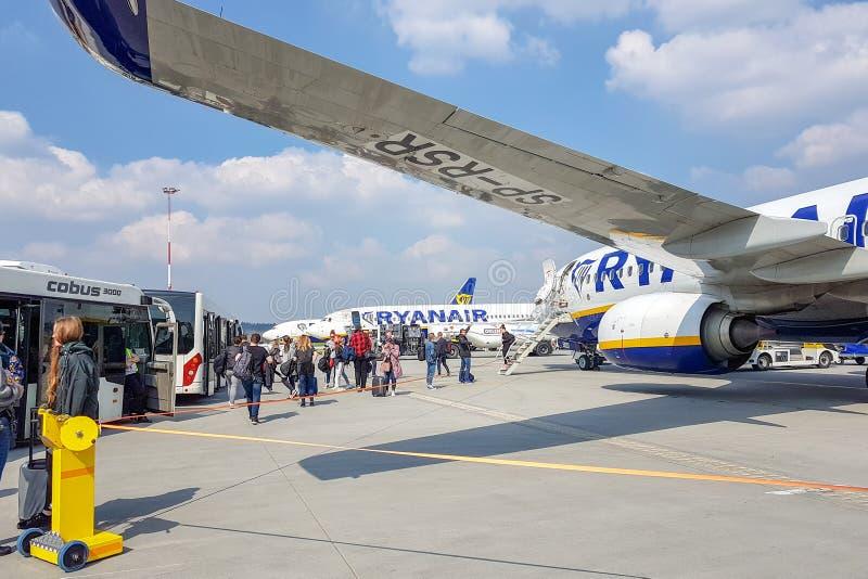 ROMA, ITÁLIA - 9 DE ABRIL DE 2019: Os passageiros saem dos aviões Rainer e sentam-se em ônibus no aeroporto foto de stock royalty free