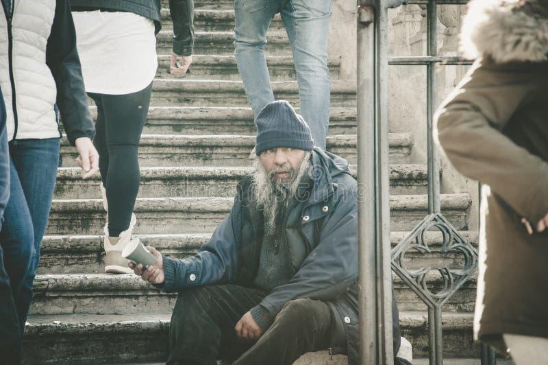 Roma, Itália - 25 de dezembro de 2017 - homem desabrigado idoso que senta-se no sta imagens de stock