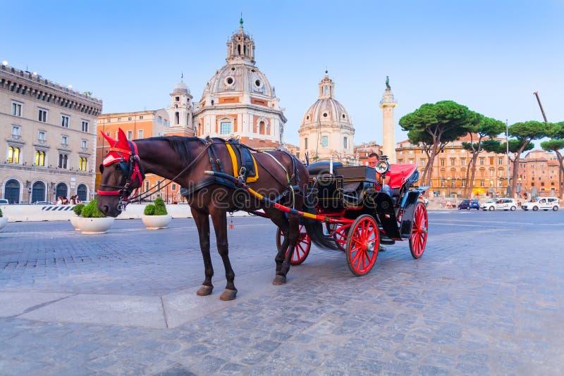ROMA, ITÁLIA - 12 de setembro de 2016: Transporte romano dos carros com rodas vermelhas, turistas de espera na praça Foro Traiano fotografia de stock