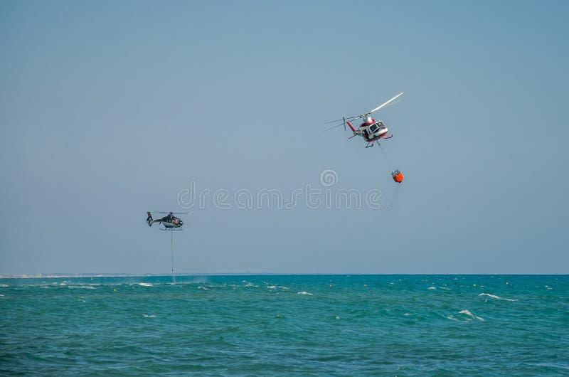 ROMA, ITÁLIA - EM JULHO DE 2017: O helicóptero do sapador-bombeiro durante a operação de salvamento recolhe a água no mar Tyrrhen fotos de stock royalty free