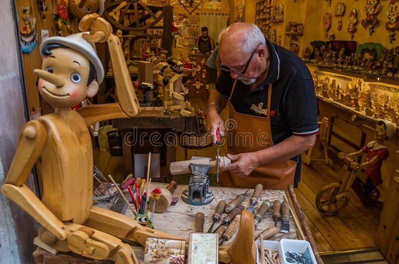 ROMA, ITÁLIA - EM JULHO DE 2017: Oficina onde o mestre examina os brinquedos de madeira tradicionais feitos a mão de Pinocchio foto de stock royalty free