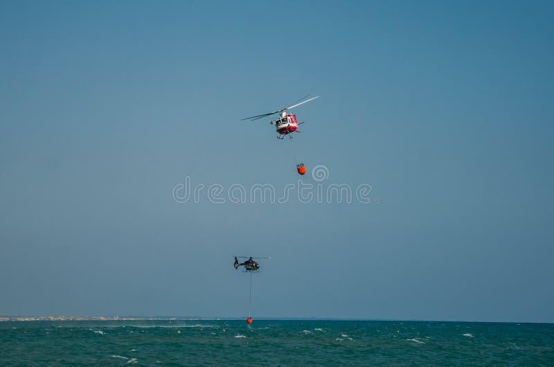 ROMA, ITÁLIA - EM JULHO DE 2017: Um helicóptero do fogo está pegarando a água em uma cesta para extinguir um fogo no mar Tyrrheni imagem de stock
