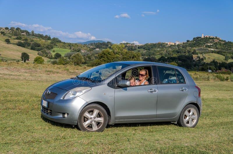 ROMA, ITALIA - AGOSTO DE 2018: Poco bebé adorable que conduce un coche de plata Toyota Yaris y su mamá están conduciendo a través imagen de archivo libre de regalías