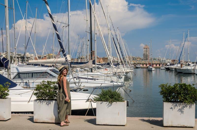 ROMA, ITALIA - AGOSTO 2018: La giovane bella ragazza cammina nel porto vicino agli yacht di lusso fotografie stock