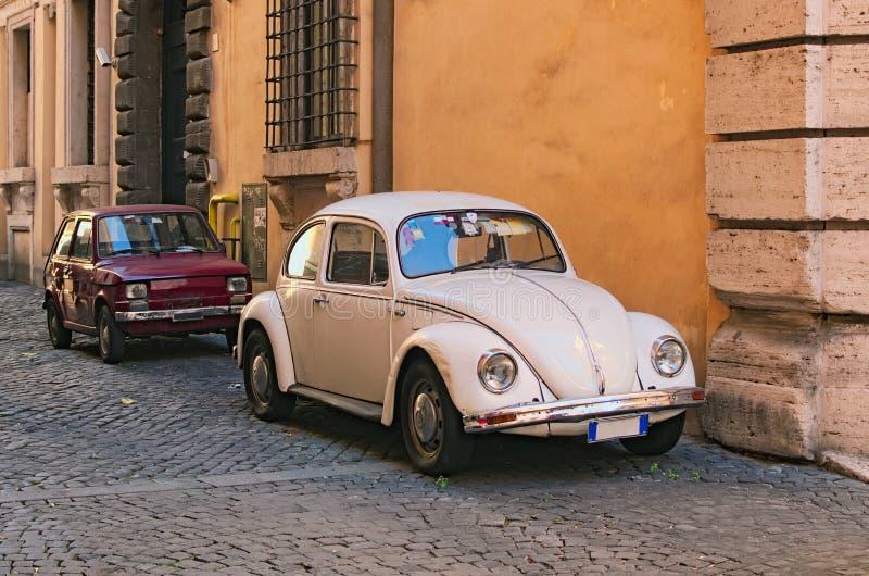 ROMA, ITALIA - 6 DE ENERO DE 2017: Dos coches del vintage parquearon en la pared del edificio foto de archivo libre de regalías