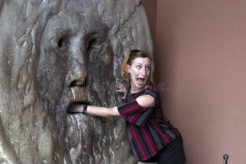 ROMA, ITALIA - 15 GIUGNO 2019 - turista che prova la bocca della maschera di verità fotografia stock libera da diritti