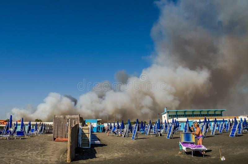 ROMA, ITALIA - JULIO DE 2017: Fuego con las nubes de humo en la playa con los paraguas y los ociosos azules del sol en Ostia, Ita fotografía de archivo