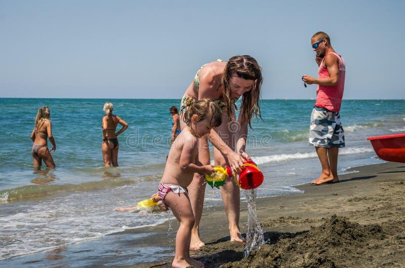 ROMA, ITALIA - JULIO DE 2017: Una familia, una madre y una hija jovenes con una natación circundan, jugando en la playa en la pla foto de archivo libre de regalías